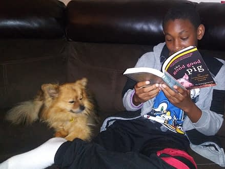 Jayden, age 12, sits down to read The Good Good Pig with his dog Monty